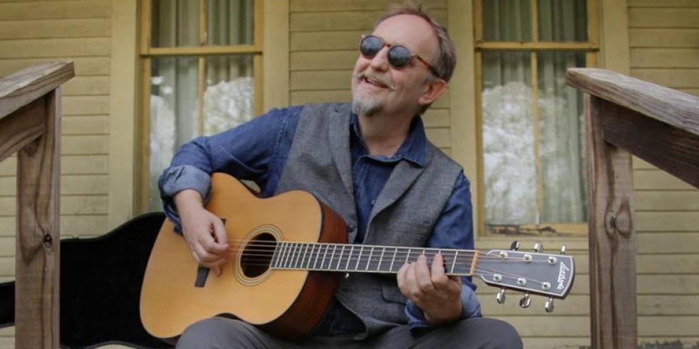 man on porch playing guitar