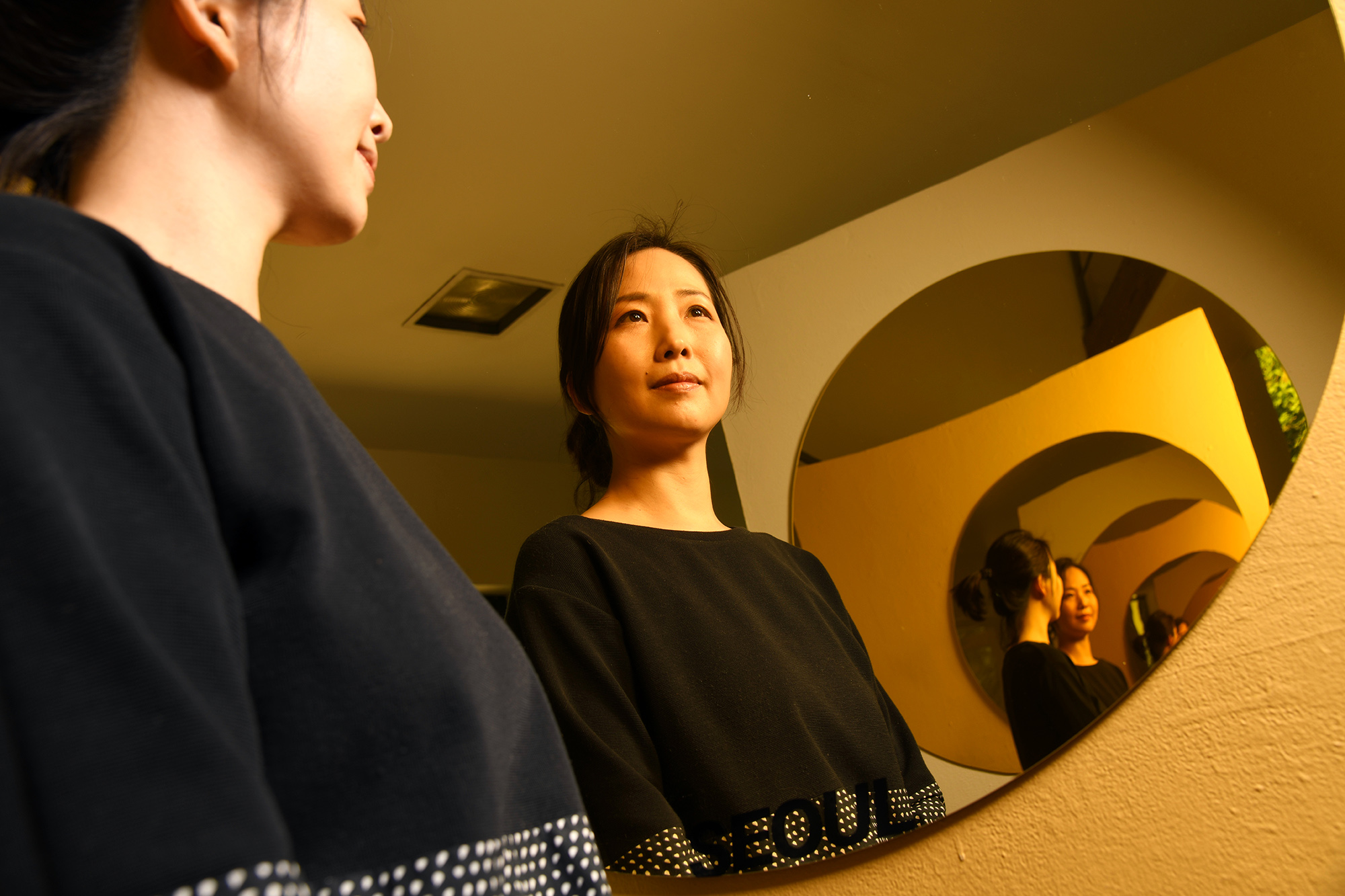 Woman standing between two mirrors
